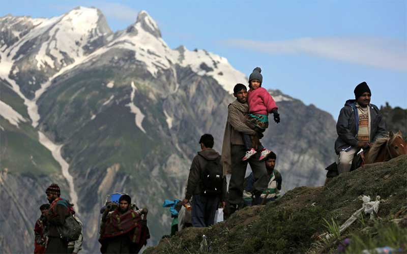 Pilgrims headed to worship at Amarnath cave in Kashmir, India, with snow capped peaks in the background