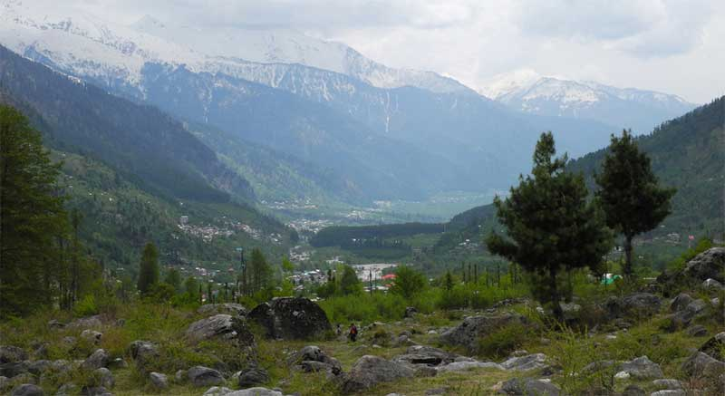 Trekking through the Kullu Valley with Himalayan peaks in the distance