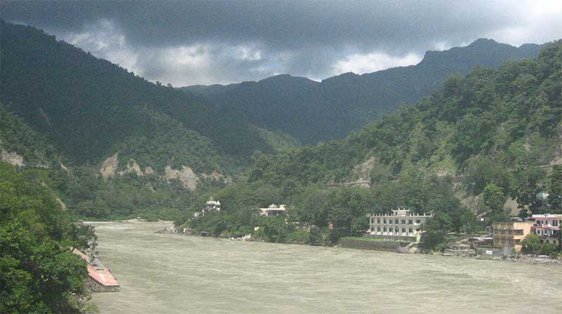 Rishikesh buildings along the riverbank, with Himalayan foothills in the background