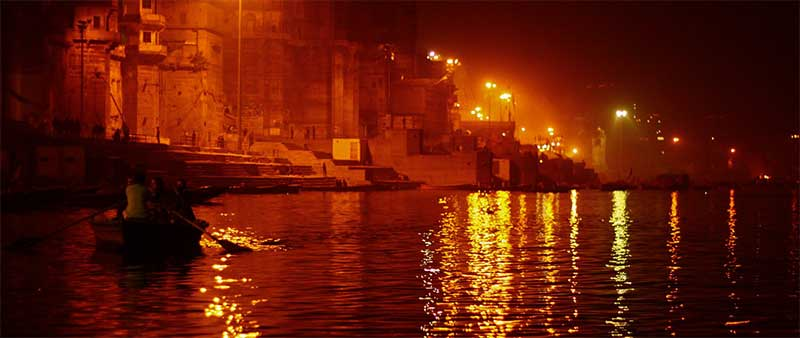 Varanasi at night with red flames over the dark water