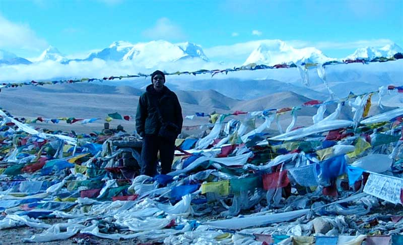 Trekker posing among payer flags with snow-capped Himalayan peaks in the background